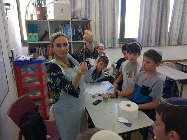 המורה מציגה את הנר שיצרה