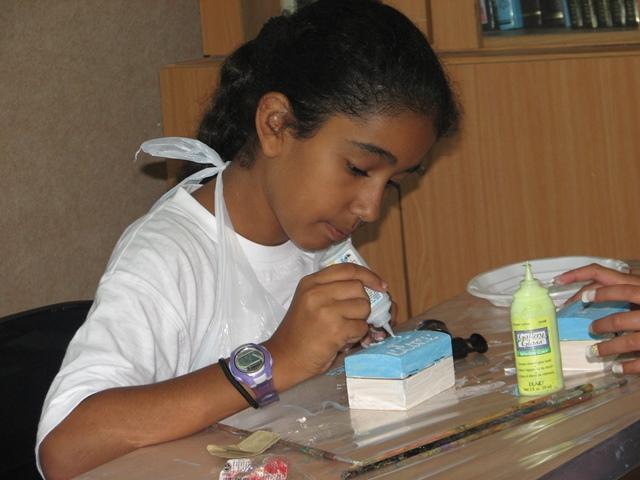 ילדה יוצרת קופת צדקה מעץ בקייטנה