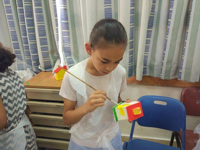ילדה צובעת קופת צדקה מעץ