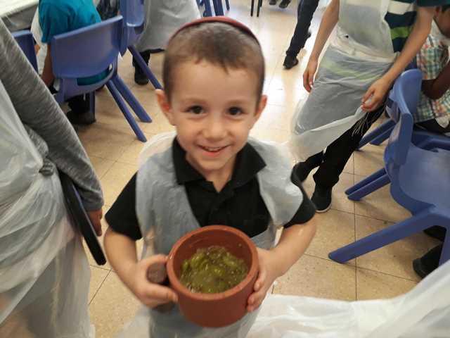 ילד מציג את הענבים שמסק